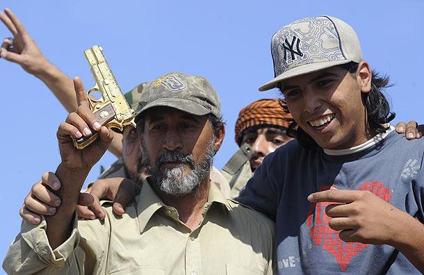 Gaddafi's gold gun-man-holds-up-colonel-gaddafi-golden-gun-pic-getty-images-181267303.jpg